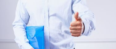 Businessman with papers holds out his hand for a handshake stock image
