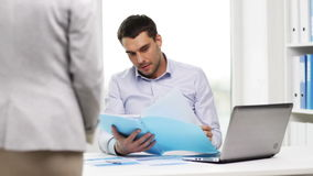 Businessman with papers and secretary in office stock footage