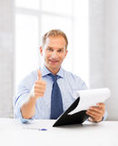 Businessman with papers showing thumbs up Royalty Free Stock Photos