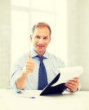 Businessman with papers showing thumbs up Stock Photo