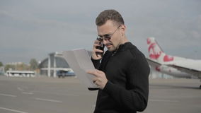 Businessman with papers talk on phone while waiting private charter in airport stock footage