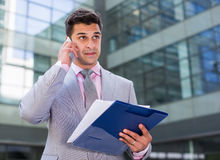 Businessman with papers talking on phone Royalty Free Stock Images