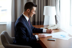 Businessman with papers working at hotel room Stock Photos