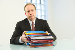 Businessman with paperwork. A view of a middle aged businessman sitting at a table or desk, holding a stack of file folders and paperwork Stock Images