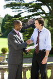 Businessman with paperwork shaking hands with associate outdoors, side view Royalty Free Stock Image
