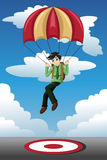 Businessman with a parachute landing on a target Stock Photography