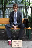 Businessman in park with executive for rent sign Royalty Free Stock Image