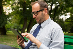 Businessman at the park with tablet  Royalty Free Stock Image