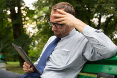 Businessman at the park with tablet sitting on a bench. Royalty Free Stock Photos