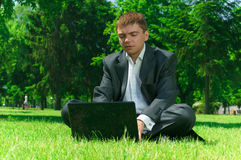 Businessman in a park workin on laptop Stock Image