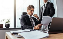 Businessman partners reading some paperwork. Businessman reading a contract document with male partner standing by in office. Businessman with partner reading Royalty Free Stock Photo