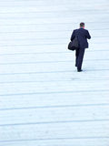 Businessman passerby. Businessman in black suit carrying handbag going across concrete square Royalty Free Stock Image