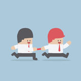 Businessman passing baton to the other in relay race Royalty Free Stock Photography
