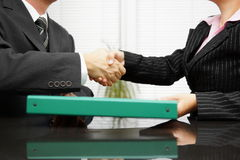 Businessman is passing binder with documentation to his client. While handshaking stock image