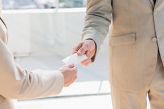 Businessman passing card to businesswoman Stock Image