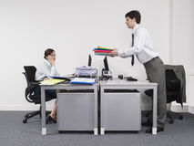 Businessman Passing Folders To Female Colleague In Office Royalty Free Stock Image