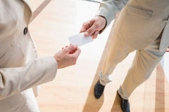 Businessman passing his card to businesswoman Royalty Free Stock Images