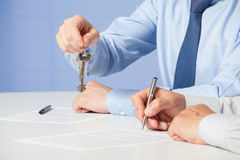 Businessman passing keys to his partne Stock Photo