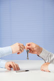 Businessman passing keys to his partner Stock Photo