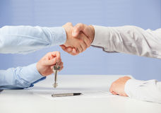Businessman passing keys to his partner and shaking his hand Stock Image