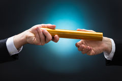 Businessman Passing Relay Baton To Colleague. Cropped hand of businessman passing golden relay baton to colleague against blue background stock image
