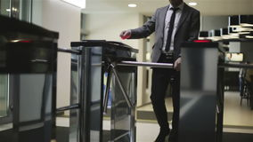 The businessman is passing through a turnstile. A man in a jacket and white shirt opens turnstile via card and comes into a business center stock footage