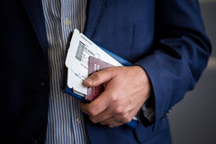 Businessman with passport and boarding pass at the airport. Businessman with passport and boarding pass waits to on boarding at the airport Royalty Free Stock Photo