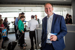 Businessman with passport and boarding pass at the airport Royalty Free Stock Photos