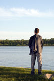 Businessman at Peace. A businessman relaxing by a small lake after work Stock Photography