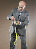 Businessman Pealing Apple. Middle aged businessman pealing an apple against brown background Stock Photos