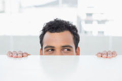 Businessman peeking behind the desk at office Stock Image