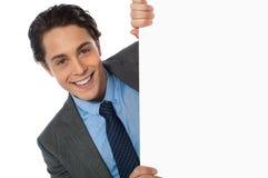 Businessman peeking behind a whiteboard Stock Image