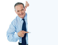 Businessman peeking behind a whiteboard Stock Image