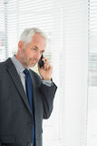 Businessman peeking through blinds while on call in office Royalty Free Stock Photography