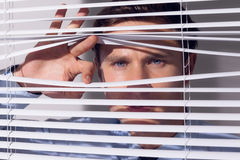 Businessman peeking through blinds Stock Photos