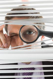 Businessman peeking through blinds with magnifying glass Royalty Free Stock Image