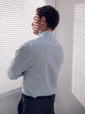 Businessman peeking through blinds in office. Rear view of a young businessman peeking through blinds in office Royalty Free Stock Photo