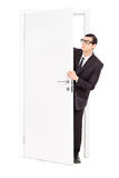 Businessman peeking through an opened door Royalty Free Stock Image