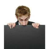 Businessman peeking at sign Stock Photo