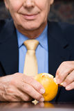 Businessman peeling an orange Royalty Free Stock Image