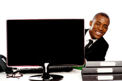 Businessman peeping from behind lcd monitor Royalty Free Stock Photos
