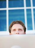 Businessman peering over laptop stock photo