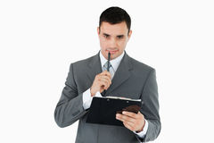 Businessman with pen and clipboard Stock Image