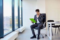Businessman with pen in hand reading, thinking over contract pap Royalty Free Stock Photo
