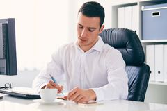 Businessman with a pen in the office. Young businessman with a pen in the office, toned royalty free stock photos