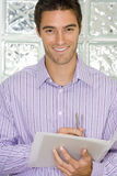 Businessman with pen and paperwork by glass block wall, smiling, portrait, close-up Stock Photo