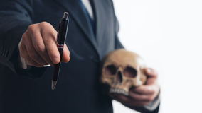 Businessman with Pen and Skull. Businessman gives a pen while holding a skull in his hand Royalty Free Stock Photography