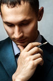 Businessman with pen thinking Royalty Free Stock Photo