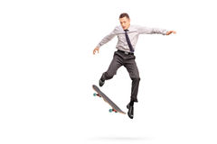 Businessman performing a trick with a skateboard stock images