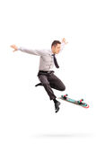 Businessman performing tricks with skateboard Stock Photos